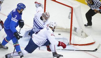 Italy's Markus Gander, left, scores past France's Cristobal Huet during the Group A preliminary round match between France and Italy at the Ice Hockey World Championship in Minsk, Belarus, Sunday, May 11, 2014. (AP Photo/Sergei Grits)