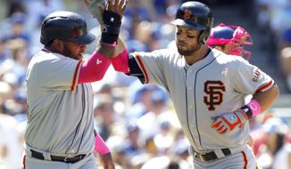 San Francisco Giants' Pablo Sandoval, left, congratulates Brandon Hicks for hitting a two-run home run in the seventh inning of a baseball game against the Los Angeles Dodgers on Sunday, May 11, 2014, in Los Angeles. (AP Photo/Alex Gallardo)