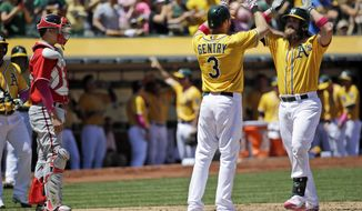 Oakland Athletics' Derek Norris, right, celebrates his second three-run home run of a baseball game with teammate Craig Gentry (3) as Washington Nationals catcher Jose Lobaton, left, watches during the second inning on Sunday, May 11, 2014, in Oakland, Calif. (AP Photo/Marcio Jose Sanchez)