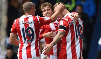 Stoke City's Marko Arnautovic, right, celebrates with teammates Marc Muniesa, center, and Jonathan Walters after forcing West Bromwich Albion's Gareth McAuley into scoring an own goal during, their English Premier League soccer match at The Hawthorns, West Bromwich, England, Sunday, May 11, 2014. (AP Photo/Joe Giddens, PA Wire)    UNITED KINGDOM OUT   -   NO SALES   -   NO ARCHIVES