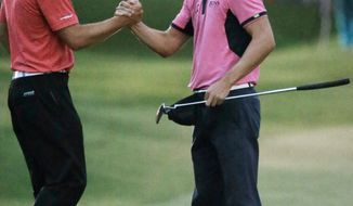 Martin Kaymer of Germany, right, shakes hands with Jordan Spieth on the 18th green during the final round of The Players championship golf tournament at TPC Sawgrass, Sunday, May 11, 2014 in Ponte Vedra Beach, Fla. Kaymer won the championship. (AP Photo/John Raoux)
