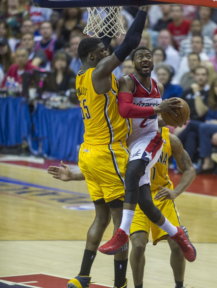 Wizards' John Wall collides with Pacers' Roy Hibbert under the basket and misses the shot in the fourth quarter as the Washington Wizards host the Indiana Pacers for Game 4 of the Eastern Conference semifinal playoff series at the Verizon Center in Washington, DC, Sunday, May 11, 2014. Wall was held to only 12 points in the game as the Wizards lost to the Pacers 95-92. (Photo Rod Lamkey Jr.)