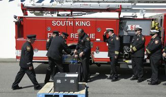 South King Co. Fire and Rescue officials look on Monday, May 12, 2014, during the delivery of a piece of limestone that was part of the building at the Pentagon in Washington, DC, before it was destroyed in the September 11, 2001 terrorist attacks. The stone was delivered during a ceremony at the Alaska Airlines cargo facility in Seatac, Wash., and will be part of a Sept. 11th memorial in Federal Way, Wash. that will be dedicated on Sept. 11, 2014, and also contains a beam from the World Trade Center in New York and a rock from the field in Shanksville, Pa., where United flight 93 crashed during the attacks. (AP Photo)