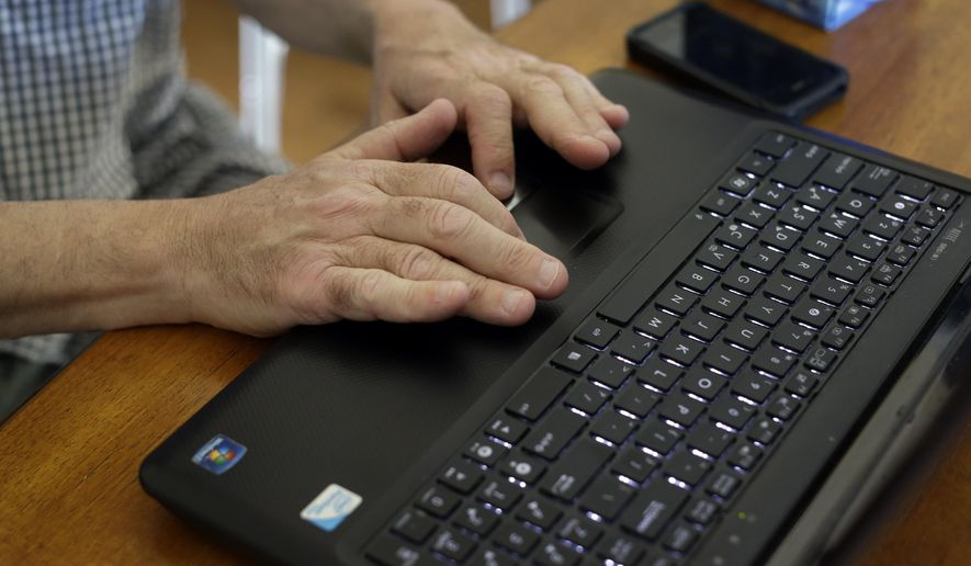 This photo taken May 8, 2014 shows Mark Matulaitis working on his laptop that he uses for virtual house calls with his neurologist in his home in Salisbury, Md. Matulaitis has had Parkinson's disease since 2011 and sees a neurologist at the University of Rochester via his laptop and special Skype-like software.  (AP Photo/Patrick Semansky)