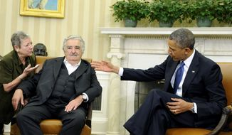 President Barack Obama looks at the translator, left, as he speaks during a press availability with Uruguay's President Jose Mujica in the Oval Office of the White House in Washington, Monday, May 12, 2014. (AP Photo)