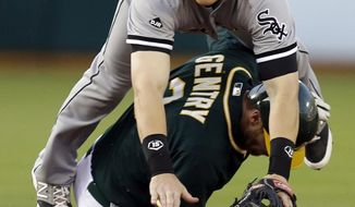 Chicago White Sox second baseman Gordon Beckham, top, is upended by Oakland Athletics' Craig Gentry in the first inning of a baseball game Monday, May 12, 2014, in Oakland, Calif.  Athletics' Josh Donaldson was out at first base on the failed double play. (AP Photo/Ben Margot)