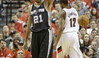 San Antonio Spurs' Tim Duncan (21) points after fouling as Portland Trail Blazers' LaMarcus Aldridge (12) walks on in the first quarter during Game 4 of a Western Conference semifinal NBA basketball playoff series Monday, May 12, 2014, in Portland, Ore. (AP Photo/Rick Bowmer)