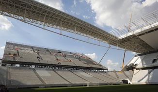 Men work on the Itaquerao stadium in Sao Paulo, Brazil, Thursday, May 8, 2014. The still unfinished stadium will host the World Cup opener match between Brazil and Croatia on June 12. (AP Photo/Andre Penner)
