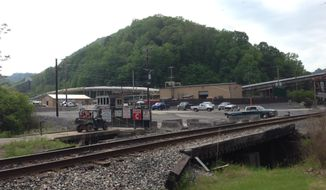 Vehicles are parked outside the Brody Mine No.1 in Wharton, W.Va., Tuesday May 13, 2014.  Two workers died after they were trapped as the ground failed at the West Virginia coal mine.  The ground failure occurred just about 8:45 p.m. Monday, trapping the workers, safety agency officials said.  The miners' bodies were recovered, and safety personnel were on the site of Brody Mine No. 1 in Boone County, about 50 miles south of Charleston.  Preliminary indications show that a coal burst was responsible, according to state officials and mine owner Patriot Coal. (AP Photo/Charleston Daily Mail, Marcus Constantino)