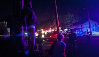 La'keya Brown, 11, of Flint stands atop a raised curb as she watches firefighters and police officers investigate a one-story home that exploded after midnight, Tuesday, May 13, 2014 in Flint. Authorities say a suspected natural gas explosion leveled a vacant Flint house, damaging nearby homes and injuring some people nearby.  (AP Photo/The Flint Journal, Jake May) LOCAL TV OUT; LOCAL INTERNET OUT