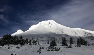 File--In this Oct. 2, 2013, clouds lift briefly and allow the sun to highlight Mount Hood wearing a fresh coat of snow near Government Camp, Ore.  The Hood River County Sheriff's Office says a climber appeared to be alone when he fell on the mountain early Tuesday.  Rescuers believe they've located the climber on Mount Hood who was seen falling about 1,000 feet by other climbers on Oregon's tallest peak. (AP Photo)