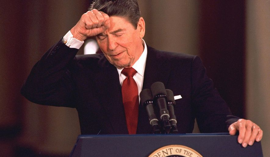 "FILE - In this March 19, 1987 file photo, President Ronald Reagan taps his forehead at the White House while responding to a reporter's question during a news conference at which he said he never deliberately lied to the public, despite admitting to a misstatement about Israeli involvement in the Iran-Contra affair. In a 1986 radio address admitting to missteps in the Iran-Contra scandal, the president famously said ""mistakes were made"" - a passive acknowledgement of wrongdoing that didn't directly implicate anyone. (AP Photo/Dennis Cook, File)"