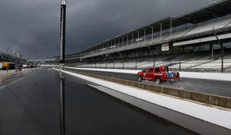 The scoring pylon is reflected in standing water in the pits area as heavy storms halted practice for the Indianapolis 500 IndyCar auto race at the Indianapolis Motor Speedway in Indianapolis, Tuesday, May 13, 2014. (AP Photo)