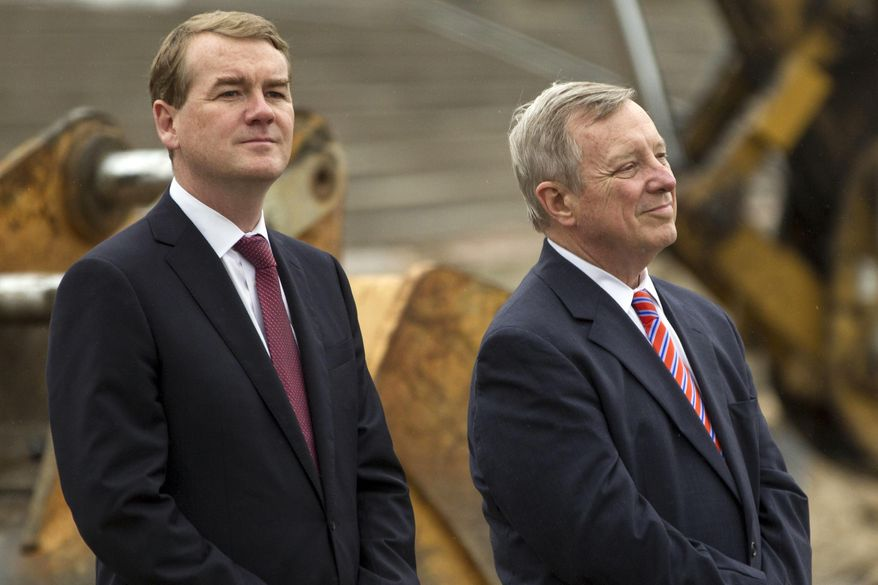 Sen. Michael Bennet, D-Colo., left, and Sen. Dick Durbin, D-Ill., listen as Vice President Joe Biden speaks during a visit to the CityArchRiver project at the Gateway Arch on Tuesday, May 13, 2014, in St. Louis. (AP Photo/Whitney Curtis)