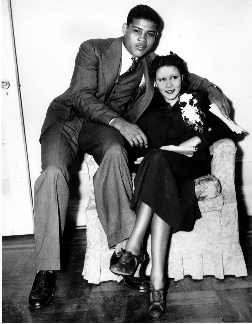 Heavyweight boxer Joe Louis poses with his bride, Marva Trotter, after his fight with Max Baer in New York on Sept. 24, 1935. The couple married a few hours before the fight, in which Louis scored a knockout victory against the former heavyweight champion. (AP Photo)