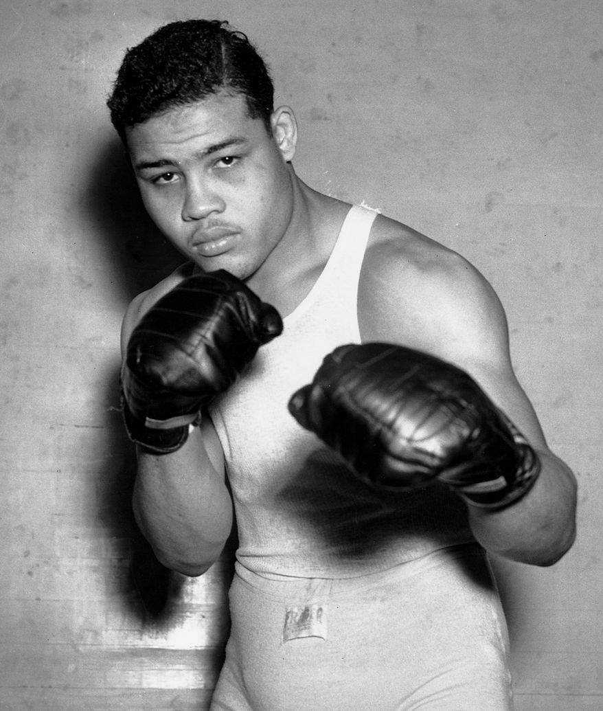 Fighter Joe Louis, nicknamed the Brown Bomber, poses in his boxing apparel in Pompton Lakes, N.J. on Jan. 24, 1937. Louis achieved the world heavyweight title in June 1937 and held it until May 1949. (AP Photo)