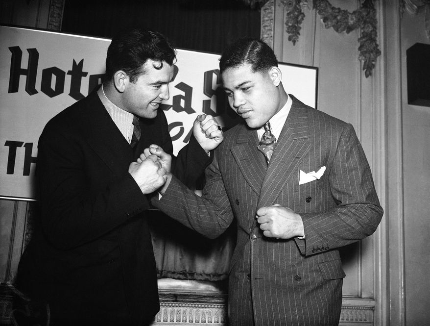 Jim Braddock, left, and Joe Louis struck these poses with good humor, Feb. 19, 1937 after signing to participate in a heavyweight title bout in Comiskey Park on June 22. On that day in June there?ll likely be no such friendliness in evidence. (AP Photo)