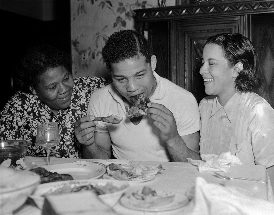 New  heavyweight boxing champion Joe Louis eats his mother's fried checken when her returned to Detroit June 25, 1937 after whipping Jim Braddock in Chicago.   At left is Louis' mother Lilly Barrow Brooks, and at right, is his wife Marva.   (AP Photo)