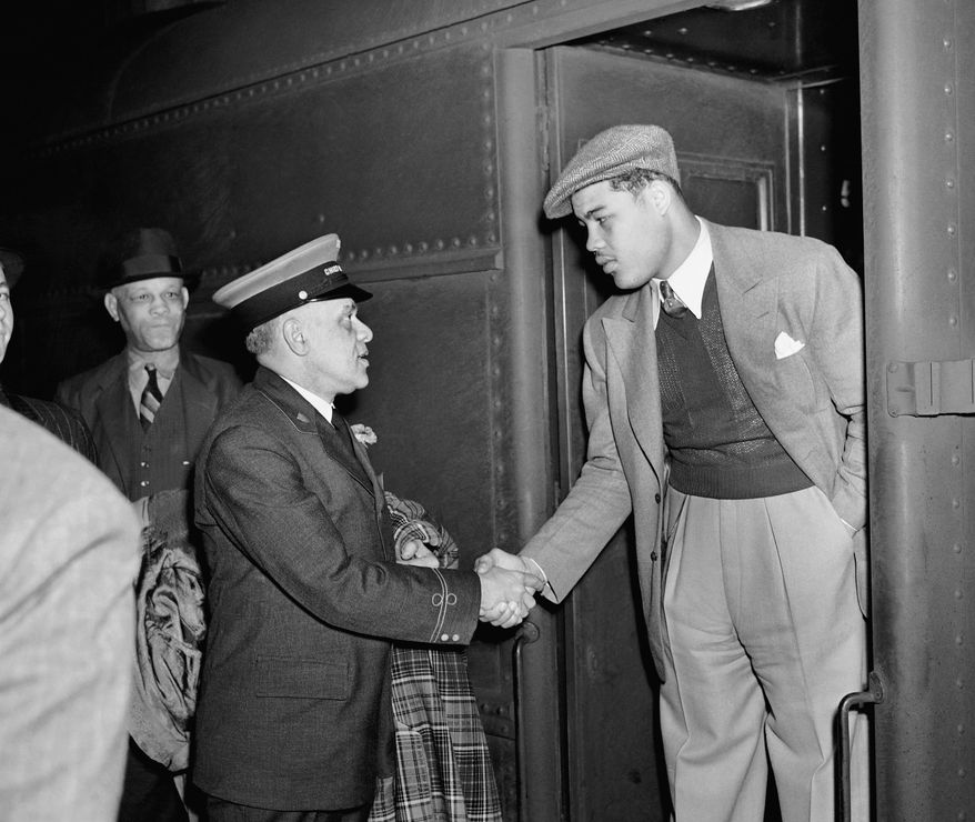 Joe Louis, heavyweight champ, breezed into Grand Central Station, at New York City, May 11, 1938 in sports clothes and cap.   He came to New York to sign up to fight Max Schmeling at Yankee Stadium June 22, 1938   Here he gets the grip of friendship from Jim Williams, chief porter and the nation's original redcap.  (AP Photo)