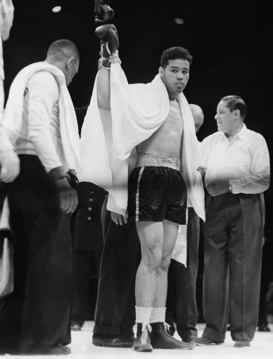 Joe Louis raises his right arm as he reaches the peak of his career after he knocked out Max Schmeling in the first round at  Yankee Stadium June 22, 1938 in New York.  This was the second fight between the two heavyweights, a rematch that created world wide interest.   Schmeling was sent to the canvas several times with referee Arthur Donovan making Louis the winner, by a knockout, two minutes and four seconds into the first round.      (AP Photo)