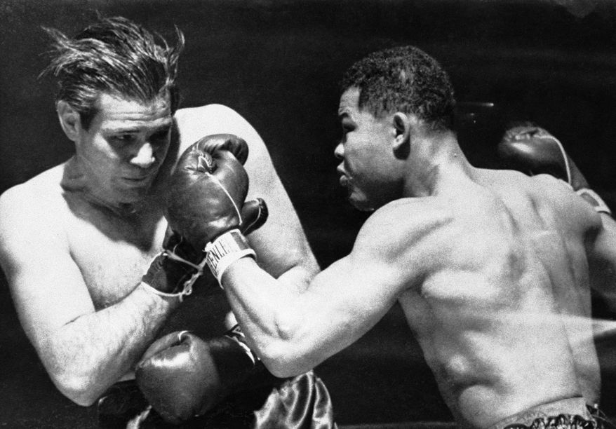 American boxer Buddy Baer, left, uses his glove to block a left-handed blow by champion Joe Louis just before the title-holder knocked out the challenger in the first round of their title fight at Madison Square Garden in New York on Jan. 9, 1942. The time token in disposing of the challenger was two minutes 56 seconds. (AP Photo)