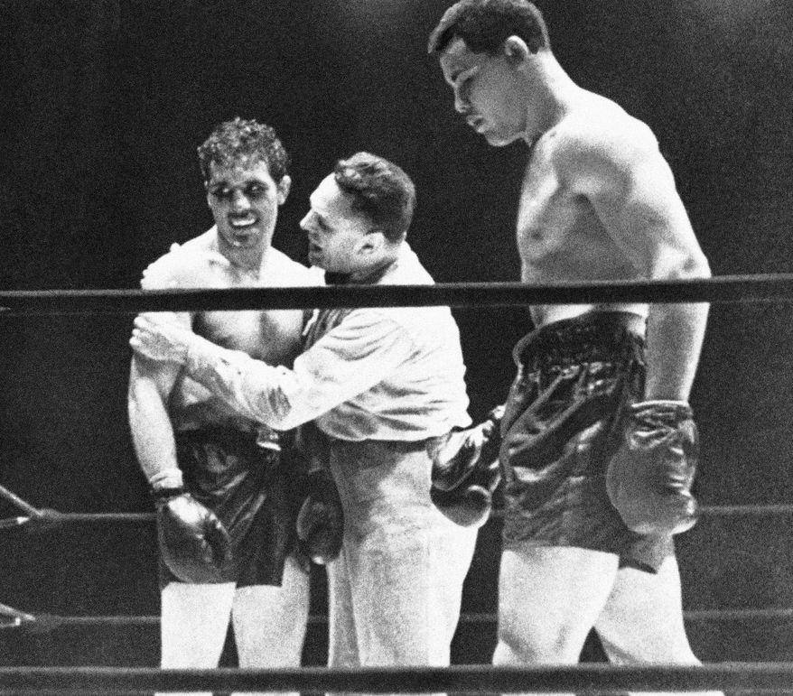 Referee Eddie Joseph, center, wrapps his arms around Billy Conn, left, during the World Heavyweight Championship bout with  Joe Louis, in New York, June 18, 1941. (AP Photo) (AP Photo)