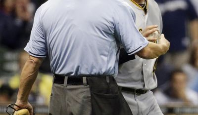 Home plate umpire Dale Scott talks to Pittsburgh Pirates starting pitcher Gerrit Cole, right, after Cole hit Milwaukee Brewers' Carlos Gomez with a pitch during the third inning of a baseball game Tuesday, May 13, 2014, in Milwaukee. (AP Photo/Morry Gash)