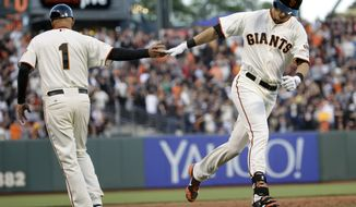 San Francisco Giants' Tyler Colvin, right, shakes hands with third base coach Tim Flannery, left, after Colvin's solo home run against the Atlanta Braves during the second inning of a baseball game on Monday, May 12, 2014, in San Francisco. (AP Photo/Marcio Jose Sanchez)