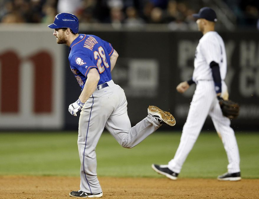 New York Mets second baseman Daniel Murphy, left, runs past New York Yankees shortstop Derek Jeter after hitting a fifth-inning, three-run, home run in a baseball game at Yankee Stadium in New York, Tuesday, May 13, 2014.  (AP Photo)