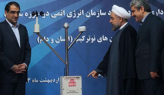 In this photo released by the official website of the office of the Iranian Presidency, Iran's President Hassan Rouhani, second right, points a UV-Index Monitoring System, a device to measure the level of the ultraviolet radiation (UV), as he unveils it in a ceremony in Tehran, Iran, Sunday, May 11, 2014. Rouhani said Sunday his country has nothing to offer except transparency in nuclear talks with world powers, rebuffing hard-liners as negotiators seek a final deal over the Islamic Republic's contested program. He is accompanied by Vice President for science and technology affairs Sorena Sattari, right, and Health Minister Hassan Hashemi. (AP Photo/ Iranian Presidency Office, Mohammad Berno)