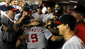 Washington Nationals left fielder Kevin Frandsen (19) celebrates with teammates after hitting a ninth inning solo home run against the Arizona Diamondbacks during a baseball game, Monday, May 12, 2014, in Phoenix. (AP Photo/Rick Scuteri)