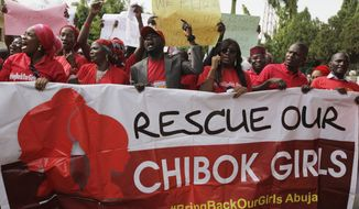 "Women attend a demonstration calling on the government to rescue the kidnapped schoolgirls of the Chibok secondary school, in Abuja, Nigeria, Tuesday, May 13, 2014. A Nigerian government official said ""all options are open"" in efforts to rescue almost 300 abducted schoolgirls from their captors as US reconnaissance aircraft started flying over this West African country in a search effort.  Boko Haram, the militant group that kidnapped the girls last month from a school in Borno state, had released a video yesterday purporting to show some of the girls. A civic leader said representatives of the missing girls' families were set to view the video as a group later today to see if some of the girls can be identified. (AP Photo / Sunday Alamba)"
