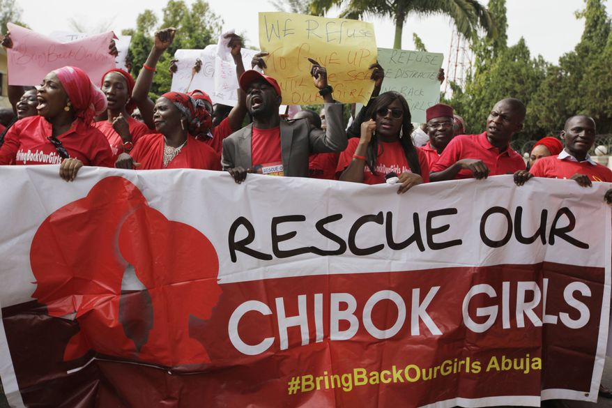 """Women attend a demonstration calling on the government to rescue the kidnapped schoolgirls of the Chibok secondary school, in Abuja, Nigeria, Tuesday, May 13, 2014. A Nigerian government official said """"all options are open"""" in efforts to rescue almost 300 abducted schoolgirls from their captors as US reconnaissance aircraft started flying over this West African country in a search effort.  Boko Haram, the militant group that kidnapped the girls last month from a school in Borno state, had released a video yesterday purporting to show some of the girls. A civic leader said representatives of the missing girls' families were set to view the video as a group later today to see if some of the girls can be identified. (AP Photo / Sunday Alamba)"""