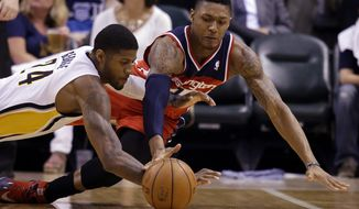 Washington Wizards guard Bradley Beal, right, and Indiana Pacers forward Paul George dives for a loose ball during the second half of game 5 of the Eastern Conference semifinal NBA basketball playoff series Tuesday, May 13, 2014, in Indianapolis. (AP Photo/Darron Cummings)