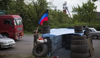"""Pro-Russian insurgents with the self-proclaimed Donetsk People's Republic man a checkpoint by the Karl Marx coal mine seen in the background near Korsun, a small town about 30 km north-east from  Donetsk, eastern Ukraine, Tuesday, May 13, 2014. The words on the wall of barricades read  """" No fascism"""". The Donetsk People's Republic has proclaimed independence from Ukraine after a contentious autonomy referendum Sunday that has been rejected by the government and the international community. (AP Photo/Alexander Zemlianichenko)"""