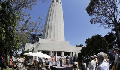 Firefighter Danny Garcia performs the National Anthem during an opening ceremony beneath Coit Tower Wednesday, May 14, 2014, in San Francisco. San Francisco's landmark Coit Tower reopened to the public Wednesday after a six-month, $1.7 million upgrade that included restoration of its famed murals. (AP Photo)