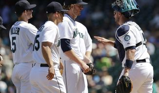 Seattle Mariners starting pitcher Brandon Maurer center, stands on the mound with catcher John Buck, right, and teammates Brad Miller, left, and Kyle Seager, second from left, berfore Maurer was pulled from a baseball game in the fourth inning against the Tampa Bay Rays, Wednesday, May 14, 2014, in Seattle. (AP Photo)