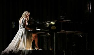 """FILE - In this Jan. 26, 2014 file photo, Taylor Swift performs """"All of Me"""" at the 56th annual Grammy Awards at Staples Center in Los Angeles. Swift has had a relationship with the """"Now That's What I Call Music"""" series for more than a decade. The series has reached No. 50, a serious milestone for a physical sales survivor that's managed to navigate all the changes in our digital world to remain relevant, profitable and incredibly consistent since its U.S. debut 16 years ago.  (Photo by Matt Sayles/Invision/AP, file)"""
