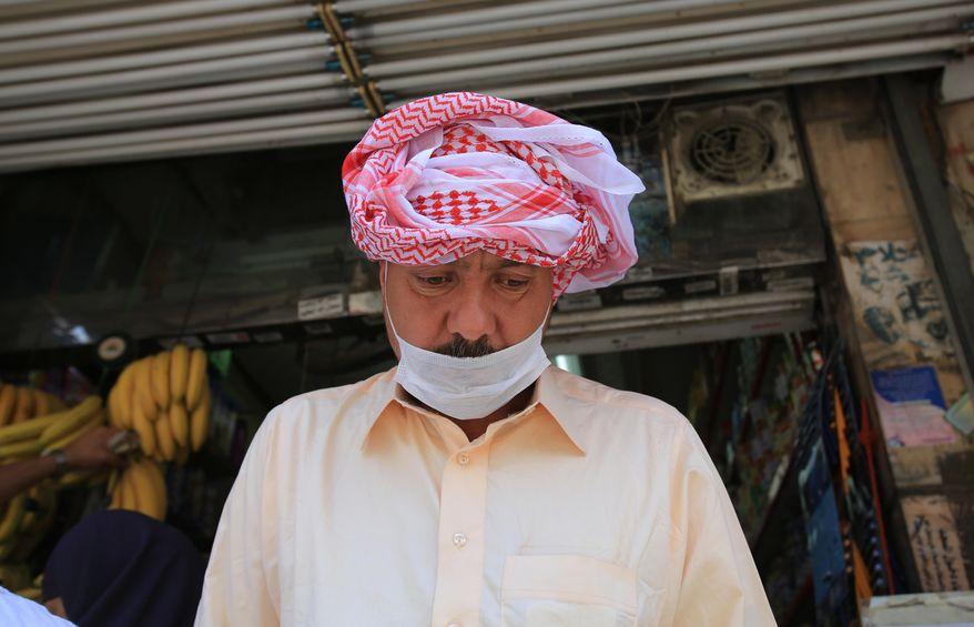 A Muslim pilgrim wears a surgical mask to help prevent infection from a respiratory virus known as the Middle East Respiratory Syndrome (MERS) in the holy city of Mecca, Saudi Arabia, Tuesday May, 13, 2014. Saudi health authorities reported another five deaths Tuesday from MERS that has sickened hundreds and killed over 150 people. (AP Photo/Hasan Jamali)