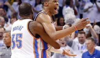 Oklahoma City Thunder forward Kevin Durant (35) celebrates with teammate Russell Westbrook, right, at the end of Game 5 of the Western Conference semifinal NBA basketball playoff series against the Los Angeles Clippers in Oklahoma City, Tuesday, May 13, 2014. Oklahoma City won 105-104. (AP Photo)