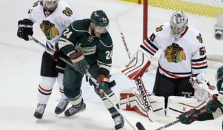 Minnesota Wild left wing Matt Cooke (24) and Chicago Blackhawks defenseman Nick Leddy (8) chase the puck as Blackhawks goalie Corey Crawford (50) covers the net during the first period of Game 6 of an NHL hockey second-round playoff series in St. Paul, Minn., Tuesday, May 13, 2014. The Blackhawks won 2-1 in overtime. (AP Photo/Ann Heisenfelt)