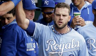 Kansas City Royals' Mike Moustakas celebrates in the dugout after hitting a three-run double during the second inning of a baseball game against the Colorado Rockies Wednesday, May 14, 2014 in Kansas City, Mo. (AP Photo/Charlie Riedel)