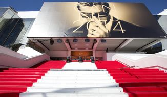 Workers prepare the red carpet on the stairs of the Palais des Festivals prior to the start of the 67th international film festival, Cannes, southern France on Wednesday, May 14, 2014. The festival runs from May 14th to May 25th. (AP Photo/Virginia Mayo)