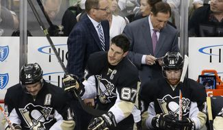 Pittsburgh Penguins' Chris Kunitz (14), Sidney Crosby (87), and James Neal (18) sit on the bench in front of coach Dan Bylsma, left rear, and assistant coach Jacques Martinin during the third period of Game 7 of a second-round NHL playoff hockey series against the New York Rangers in Pittsburgh on Tuesday, May 13, 2014. The Rangers won 2-1 and advanced to the conference finals. (AP Photo)