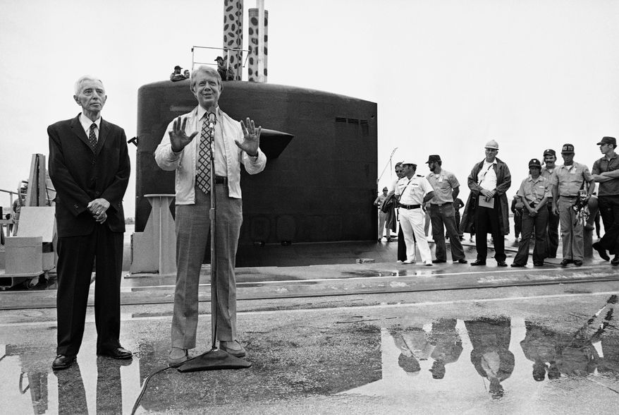President Jimmy Carter tells newsmen of his submarine ride aboard the nuclear submarine U.S.S. Los Angeles, May 28, 1977.  Adm. Hyman Rickover, left, who accompanied Carter on the all-day cruise, stands by.  In background is the conning tower of the submarine.