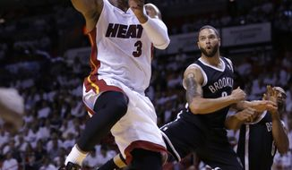 Miami Heat guard Dwyane Wade (3) goes to th basket against the Brooklyn Nets during the first half of Game 5 of a second-round NBA playoff basketball game in Miami, Wednesday, May 14, 2014. (AP Photo)