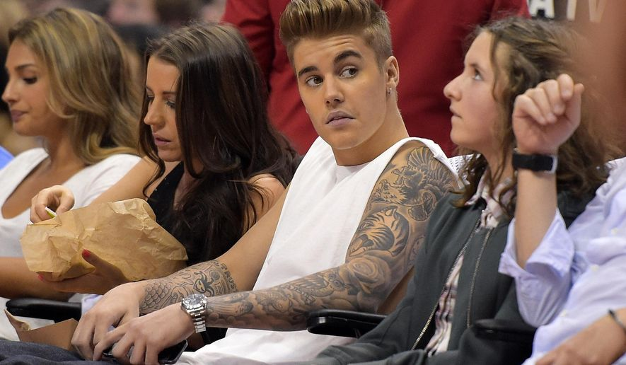 ** FILE ** This May 11, 2014, file photo shows singer Justin Bieber, center, watching the Los Angeles Clippers play the Oklahoma City Thunder with his mother Pattie Mallette, second from left, in the first half of Game 4 of the Western Conference semifinal NBA basketball playoff series in Los Angeles. (AP Photo/Mark J. Terrill, FIle )