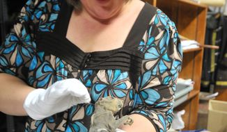 ADVANCE FOR USE SATUDAY, MAY 17, 2014 - In this photo taken on Thursday, May 8, 2014, marketing coordinator Christine Martens takes out a mummified squirrel at the Marathon County Historical Society in Wausau, Wis. (AP Photo/The Wausau Daily Herald, Txer Zhon Kha) NO SALES
