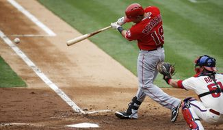 Los Angeles Angels' Efren Navarro (19) hits an RBI-single off Philadelphia Phillies starting pitcher A.J. Burnett during the second inning of an interleague baseball game, Wednesday, May 14, 2014, in Philadelphia. At right is Phillies catcher Carlos Ruiz. (AP Photo)