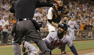 Atlanta Braves' Jason Heyward, bottom, is called safe at home by umpire Ed Hickox, left, in front of San Francisco Giants catcher Buster Posey during the sixth inning of a baseball game in San Francisco, Tuesday, May 13, 2014. Giants manager Bruce Bochy challenged the ruling but the play stood. The Braves won 5-0. (AP Photo)